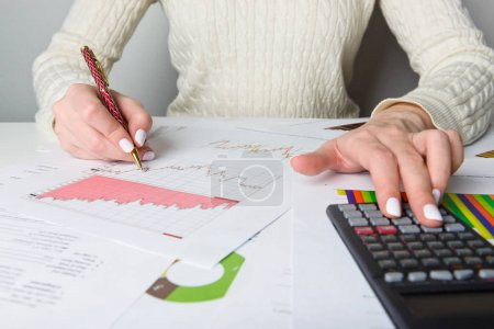 Female hands with pen, black calculator and sheets