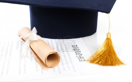 Graduation hat and Diploma on white surface