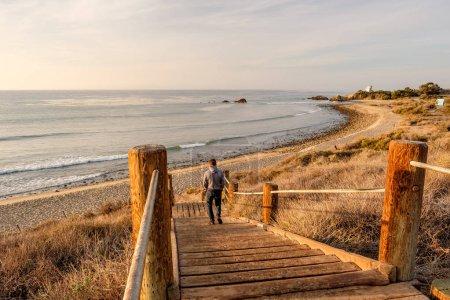 Photo pour Jeune homme marchant à boardwalk à Leo Carrillo State Beach, Malibu, Californie. - image libre de droit