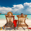 Couple in loungers on a tropical beach at Maldives...