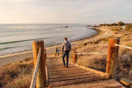 Man walking at boardwalk to beach
