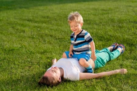 Photo for Happy smiling woman and child having fun outdoor on meadow in sunlight - Royalty Free Image