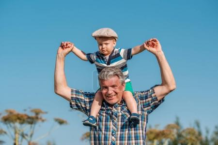 Grandfather carries grandson