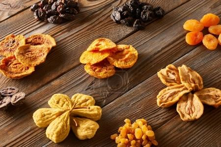 Dried fruits on rustic wooden background, top view