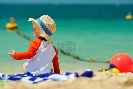 Two year old toddler boy in sun hat beach