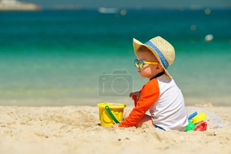 toddler boy playing with beach toys on beach