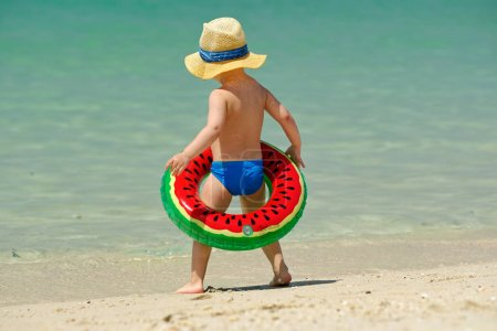 cute toddler boy in hat with inflatable swim ring on beach