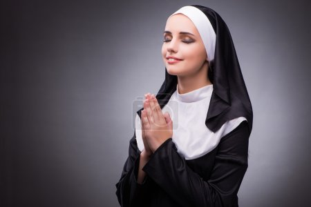 Religious nun in religion concept against dark bac...