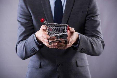 Photo pour Buisinessman tenant panier dans le concept d'achat en ligne - image libre de droit