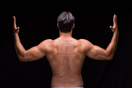 Ripped muscular man on black background