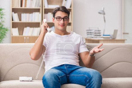 Young man talking on the phone lying in couch