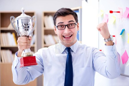Young businessman receiving prize cup in office