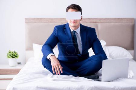 Photo pour Homme d'affaires portait un casque de réalité virtuelle dans la chambre à coucher - image libre de droit