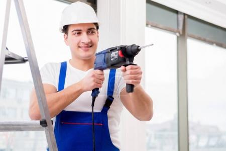 Repairman working with power drill in workshop