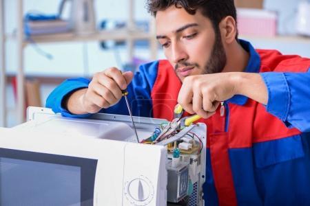 Junger Reparateur repariert Mikrowellenherd