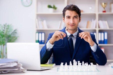 Photo pour Jeune homme d'affaires jouant aux échecs en verre au bureau - image libre de droit
