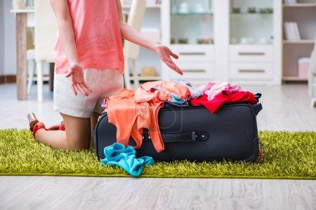 Photo pour Femme essayant d'adapter tous les vêtements à la suite avant les vacances - image libre de droit