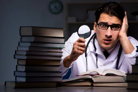Photo for Medical student preparing for university exams at night - Royalty Free Image