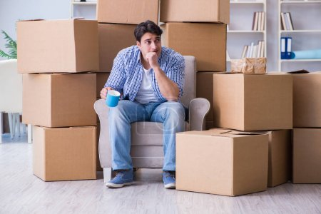 Photo for Young man moving in to new house with boxes - Royalty Free Image