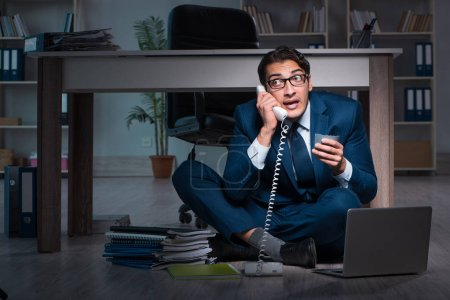 Photo for Businessman working overtime long hours late in office - Royalty Free Image