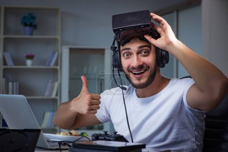 Photo for Young man playing games long hours late in the office - Royalty Free Image