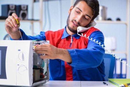 Photo pour Jeune réparateur de fixation et la réparation de four à micro-ondes - image libre de droit