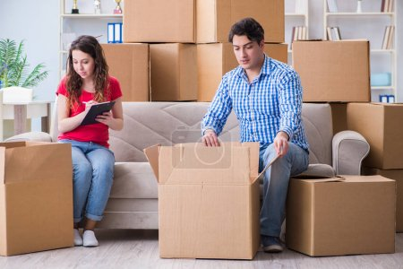 Photo for Young pair moving in to new house with boxes - Royalty Free Image