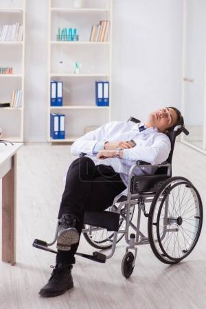 Photo for Doctor resting on wheelchair in hospital after night shift - Royalty Free Image