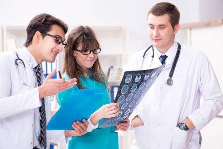 Photo pour Trois médecins discutent des résultats des radiographies - image libre de droit