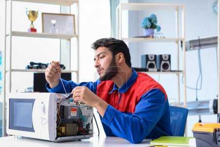 Photo for Young repairman fixing and repairing microwave oven - Royalty Free Image