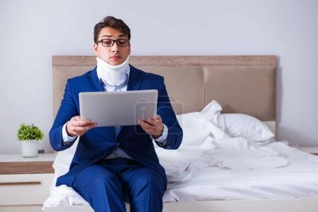 Photo pour Homme d'affaires avec blessure au cou le travail à domicile - image libre de droit