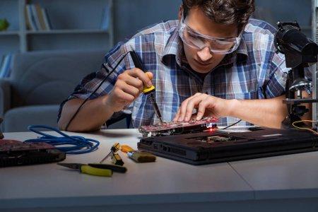 Jeune technicien de réparation soudant des pièces électriques sur le taureau