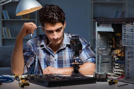 Photo for Repairman trying to repair laptop with miscroscope - Royalty Free Image