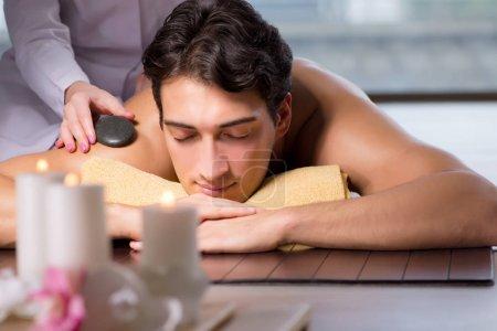 Joven hombre guapo durante el procedimiento de spa