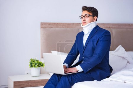 Photo for Businessman with neck injury working from home - Royalty Free Image