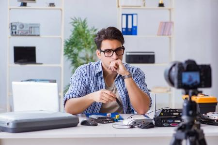 Photo for Vlogger recording computer repair on camera for vlog blog - Royalty Free Image