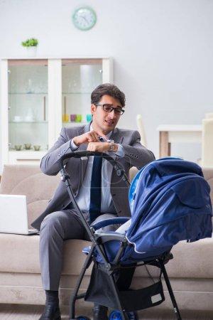 Photo pour Homme d'affaires s'occupant du nouveau-né à la maison et du télétravail - image libre de droit
