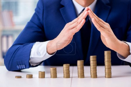 Photo pour Homme d'affaires avec des piles de pièces dans le bureau - image libre de droit
