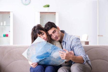 Photo pour Jeune famille discuter des plans de voyage avec carte - image libre de droit