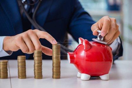 Foto de Empresario con pilas de monedas en la oficina - Imagen libre de derechos
