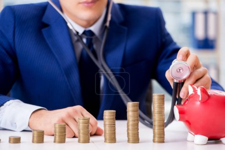 Photo pour Homme d'affaires avec des piles de pièces au bureau - image libre de droit