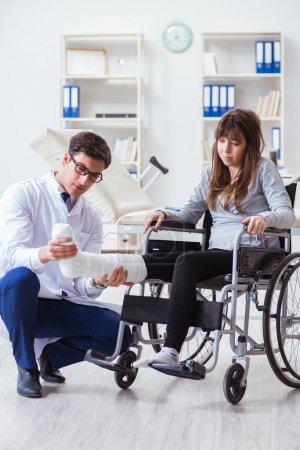Photo pour Médecin examinant une patiente en fauteuil roulant - image libre de droit