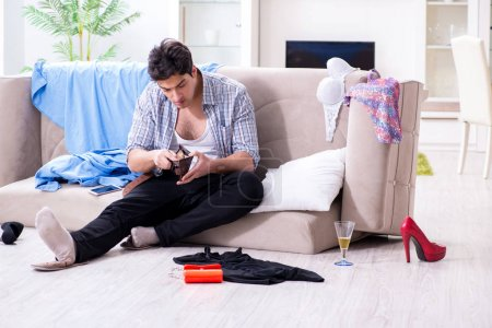 Photo for Man with mess at home after house party - Royalty Free Image