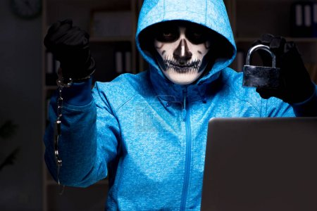 Photo for Scary hacker hacking security firewall late in office - Royalty Free Image