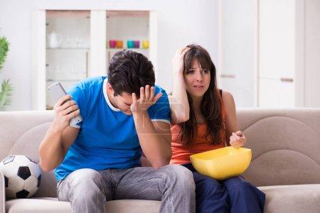 Photo pour Jeune homme regardant le football avec sa femme à la maison - image libre de droit