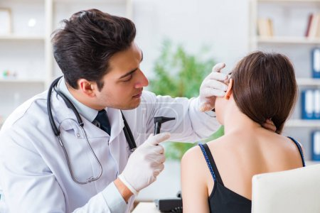 Doctor checking patients ear during medical examin...