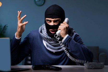 Photo for Terrorist burglar with gun working at computer - Royalty Free Image