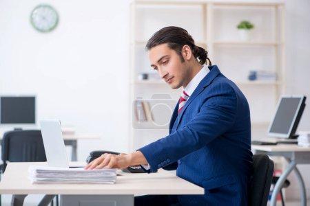Photo pour Le jeune homme d'affaires mâle s'asseyant dans le bureau - image libre de droit