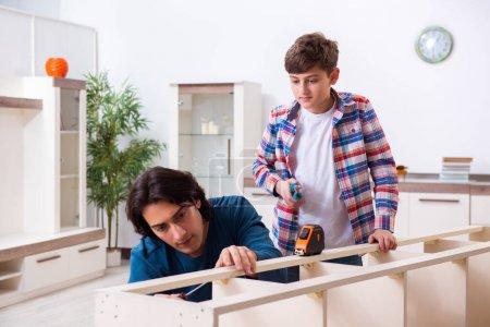 Photo pour Le jeune charpentier enseignant son fils - image libre de droit