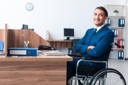 Photo pour The young male employee in wheel-chair - image libre de droit